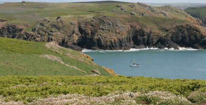 A sailing boat moored off Skomer Island